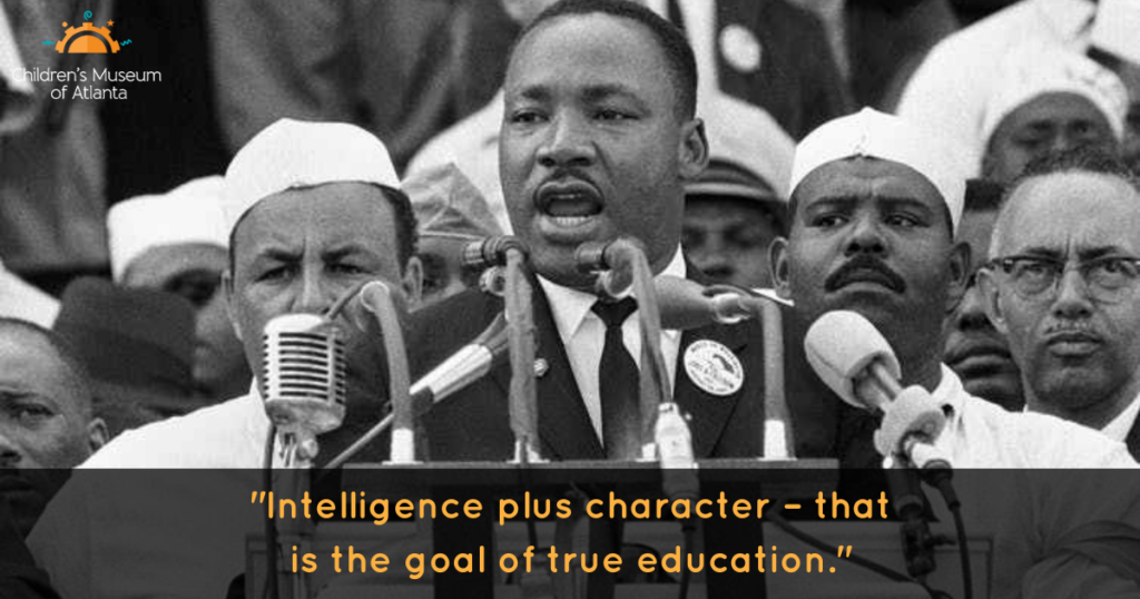 """A photo of Dr. King speaking at a pulpit in front of many microphones and with a crowd of people behind him. His quote """"Intelligence plus character - that is the goal of true education"""" is included at the bottom."""
